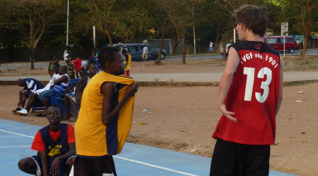 A Projects Abroad volunteer doing a basketball internship in Ghana discusses strategy during a match with a local player.